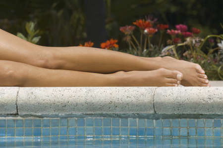 low section view: Low section view of a woman lying at the poolside