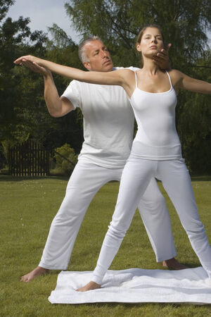 Yoga instructor teaching yoga to a young woman Stock Photo