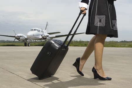 low section: Low section view of a woman pulling her luggage