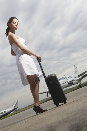 Side profile of a young woman holding her luggage at an airport