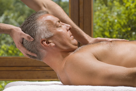 self indulgence: Side profile of a mature man receiving a massage from a massage therapist LANG_EVOIMAGES