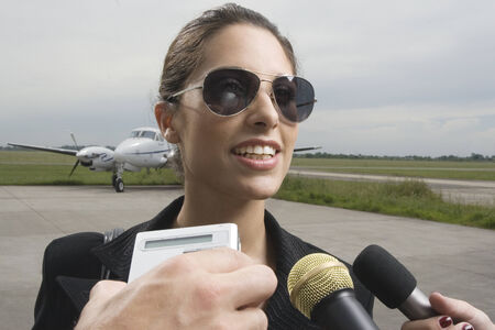 Close-up of a businesswoman giving interview at an airport