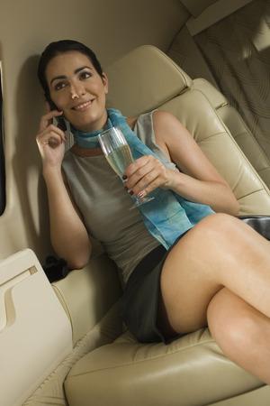 Geschäftsfrau, die in einem privaten Flugzeug LANG_EVOIMAGES