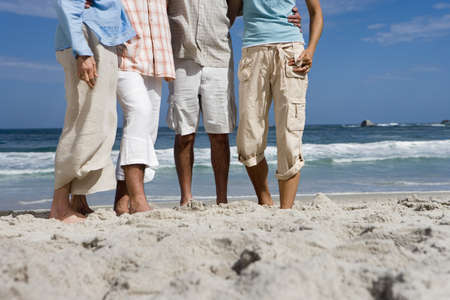 surface level: Four friends standing on sandy beach, low section, surface level LANG_EVOIMAGES