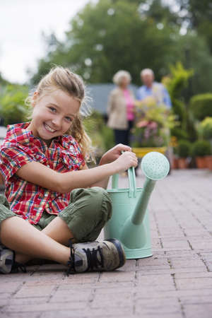 relishing: Girl (7-9) sitting with watering can in garden centre, smiling, portrait, grandparents in background