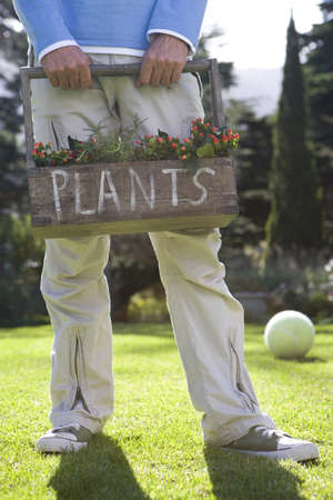 pastimes: Man holding plant box, plants written on box, football on grass in background, low section