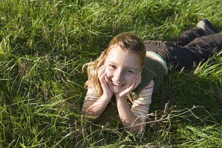 fema: Girl (7-9) lying on grass, resting hands on chin, smiling, close-up, portrait