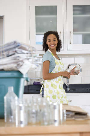 bundling: Young woman washing glass jar and can for recycling, smiling (differential focus) LANG_EVOIMAGES