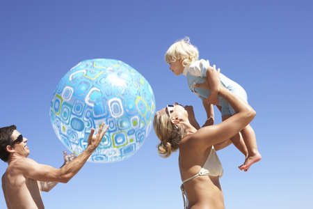 waistup: Young family playing on beach, father holding beach ball, mother lifting daughter (2-3) above head