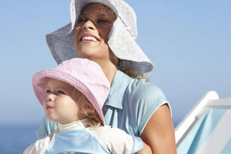 gratifying: Mother and daughter (2-3) sitting on beach in deckchair, wearing sun hats, smiling, close-up LANG_EVOIMAGES