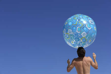 waistup: El hombre de equilibrio gran pelota de playa de color turquesa en la cabeza, vista trasera