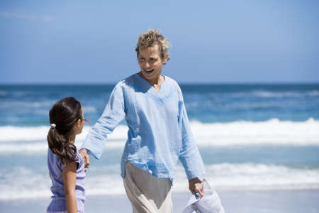 waistup: Grandmother walking with granddaughter (7-9) on beach near waters edge, smiling