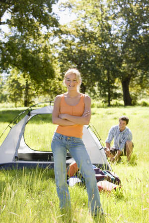 rec: Young couple assembling dome tent on camping trip in woodland clearing, focus on woman, portrait