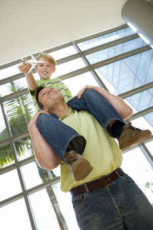 western slope: Father carrying son (8-10) on shoulders in airport, boy holding toy aeroplane, smiling, low angle view (tilt) LANG_EVOIMAGES
