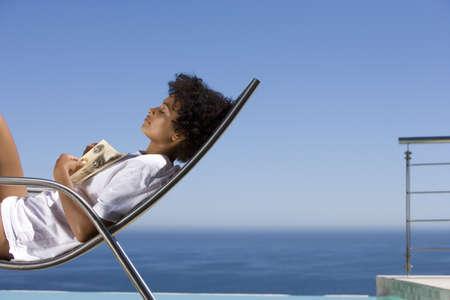waistup: Mujer joven tumbado en la silla de cubierta con el libro por mar, ojos cerrados, vista lateral