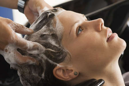 shampooing: Hairdresser shampooing womans hair in salon, close-up, profile LANG_EVOIMAGES