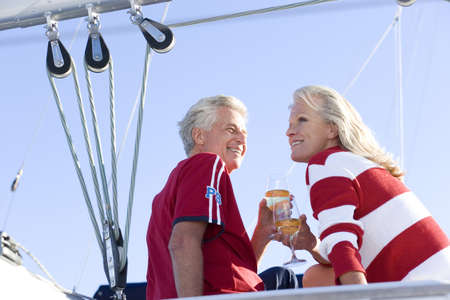 peo: Mature couple, in red jumper and t-shirt, sitting on deck of yacht moored at harbour jetty, holding wine glasses filled with champagne, smiling, low angle view