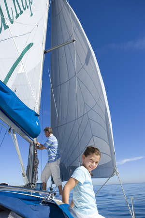 leant: Father and daughter (8-10) on deck of sailing boat, man standing beside sails, focus on girl in foreground, smiling, portrait LANG_EVOIMAGES