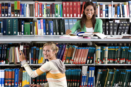 sitt: Young woman studying in library by friend taking book from shelf, smiling, portrait LANG_EVOIMAGES