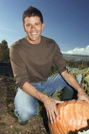 western european ethnicity: Man kneeling beside large pumpkin in vegetable garden, smiling, portrait