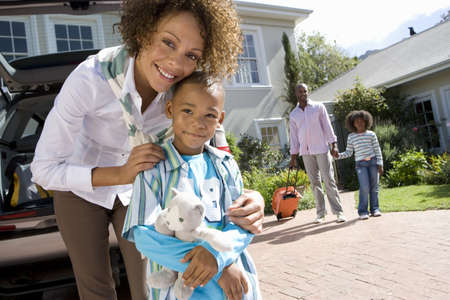 pre adult: Mother embracing son (6-8) in driveway, father and daughter (8-10) in background, smiling, portrait
