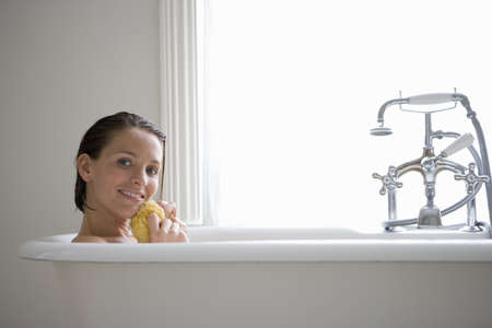 lavishly: Young woman with sponge in bath, smiling, portrait LANG_EVOIMAGES
