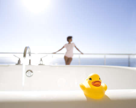 Young woman standing on balcony by sea, bath with rubber duck in foreground