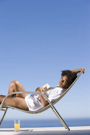 lavishly: Young woman lying on deck chair with book by sea, portrait, side view