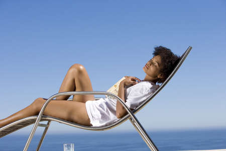 lavishly: Young woman lying on deck chair with book by sea, eyes closed, side view