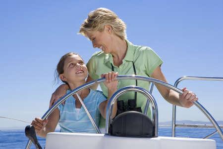 waistup: Madre e hija (8-10) de pie en el tim�n del barco de vela en el mar, direcci�n, sonriendo el uno al otro, de frente