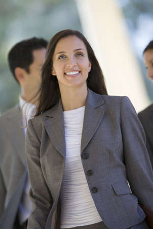 western european ethnicity: Business colleagues on the move, focus on businesswoman in foreground, smiling, portrait LANG_EVOIMAGES