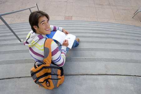 elevated view: Male student with rucksack studying on steps, smiling, portrait, elevated view