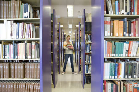 armful: Young woman with armful of books in library, smiling, portrait