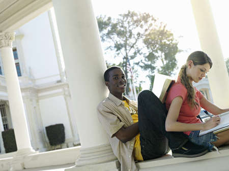 gentleman s: University students studying near colonnade, man leaning book against womans back, smiling (tilt)