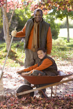 toils: Senior man and grandson (7-9) collecting autumn leaves in garden, boy sitting in wheelbarrow, smiling, portrait LANG_EVOIMAGES