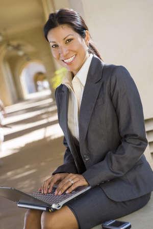 western european ethnicity: Businesswoman, in grey suit, using laptop in building arcade, smiling, side view, portrait (tilt)