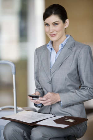 toils: Businesswoman with folder in lap, holding mobile phone, smiling, portrait LANG_EVOIMAGES