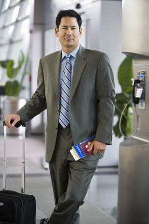 western european ethnicity: Businessman standing in airport terminal with luggage and ticket, smiling, portrait