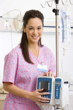 toils: Young female nurse holding IV stand in hospital ward, smiling, portrait
