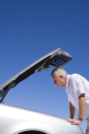 engine bonnet: Senior man experiencing car trouble, looking at engine, bonnet raised against clear blue sky, profile