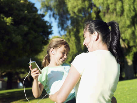 western european ethnicity: Mother and daughter (6-8) listening to MP3 player in park, sharing headphones, smiling (tilt) LANG_EVOIMAGES