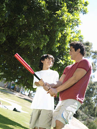 gentleman s: Father teaching son (10-12) how to hold baseball bat, standing on grass in park, smiling (tilt) LANG_EVOIMAGES