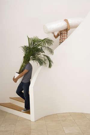 waistup: Pareja de mudarse de casa, hombre que lleva gran planta de maceta bajaba la escalera, mujer llevando la hoja de polvo