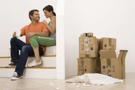 western european ethnicity: Couple moving house, taking tea break at bottom of staircase near stack of boxes, smiling