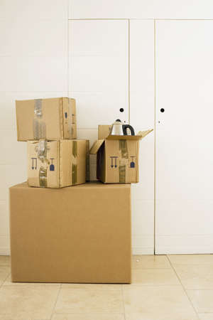 storing: Stack of large and small sealed cardboard boxes in room, kettle in open box LANG_EVOIMAGES