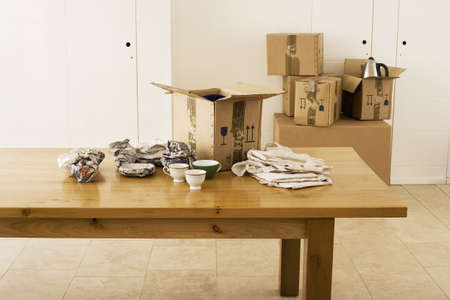bathtowel: Crockery wrapped in paper beside cardboard box on dining room table, sealed boxes in background