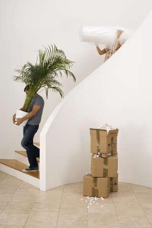 waistup: Pareja de mudarse de casa, hombre que lleva gran planta de maceta bajaba la escalera, mujer llevando hoja de polvo, el perfil