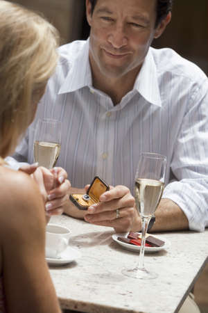 western european ethnicity: Couple dining in restaurant, focus on man holding engagement ring, proposing to woman, smiling