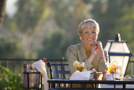 beside table: Mature woman dining at outdoor restaurant table, smiling, front view, portrait, wine in ice bucket beside table