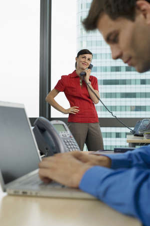 western european ethnicity: Businessman using laptop in office, focus on woman using telephone in background, smiling, side view LANG_EVOIMAGES